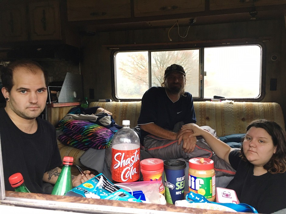 Austin Hall, left, his fiance Victoria Swan and a man who identified himself as Mark Goddard sit in one of the RVs parked on Deschutes Parkway on Washington's Capitol campus.
