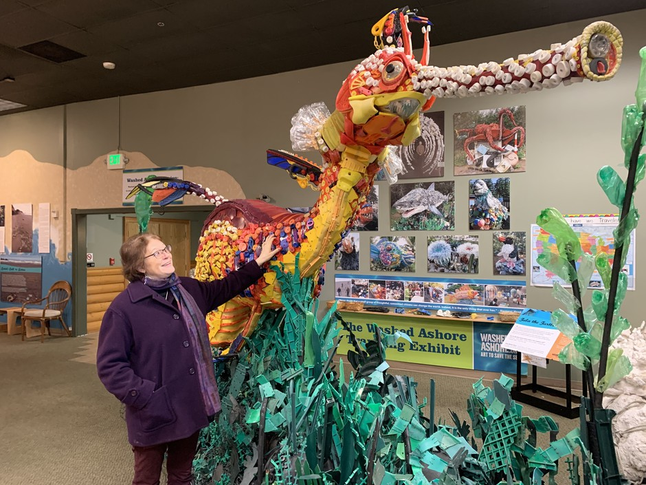 In her gallery in Bandon, Ore., Angela Haseltine Pozzi stands next to an enormous sea dragon sculpted from plastics found on Oregon's famously 'pristine' beaches.