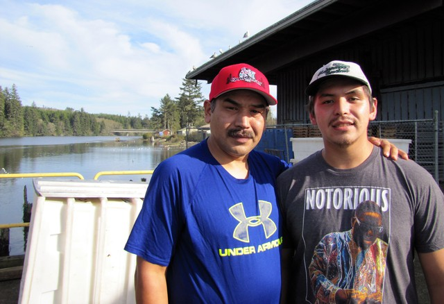 Shane Underwood (left) and his son, David, stand at the Quinault Indian Nation's seafood plant in Taholah, Washington. The loss of the largest glacier that feeds the Quinault River and rising seas are threatening the tribe's way of life.