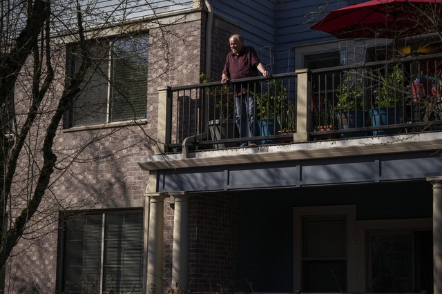Bill Bolstad stands on his balcony atHawthorne Gardens, the assisted living facility where he lives in Portland, Ore., on March 20, 2020.Homes across the state are restricting visitorsin an attempt to limit residents' chances of coming in contact with thecoronavirus.