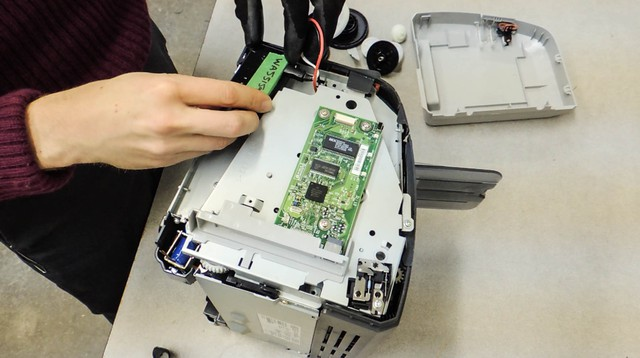 A Basel Action Network employee places a GPS tracker inside a broken printer.