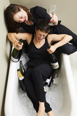 Dana Frank and Andrea Slonecker pair Champagne with laughs in a bathtub.