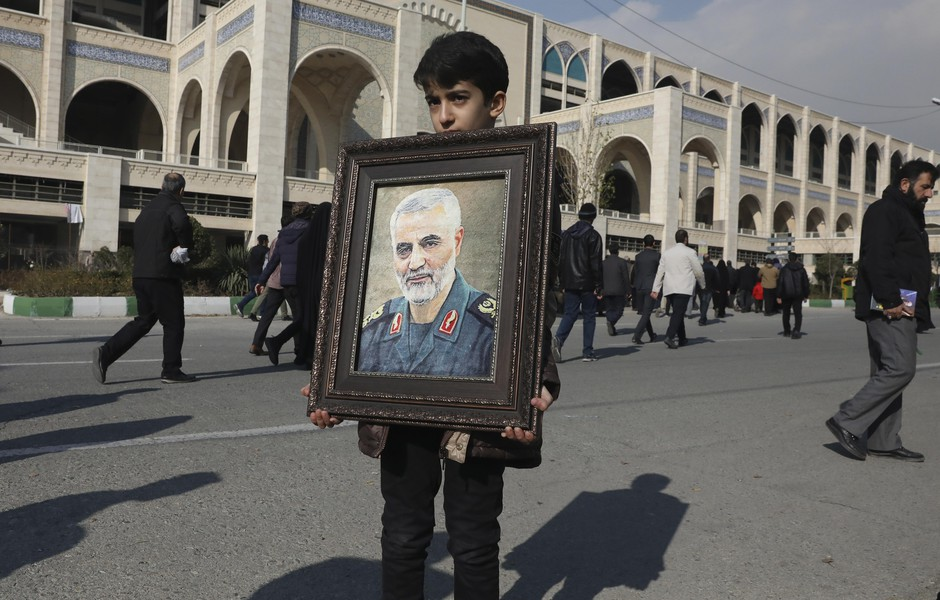 """A boy carries a portrait of Iranian Revolutionary Guard Gen. Qassim Suleimani, who was killed in the U.S. airstrike in Iraq, prior to the Friday prayers in Tehran, Iran, Friday Jan. 3, 2020. Iran has vowed """"harsh retaliation"""" for the U.S. airstrike near Baghdad's airport that killed Tehran's top general and the architect of its interventions across the Middle East, as tensions soared in the wake of the targeted killing."""