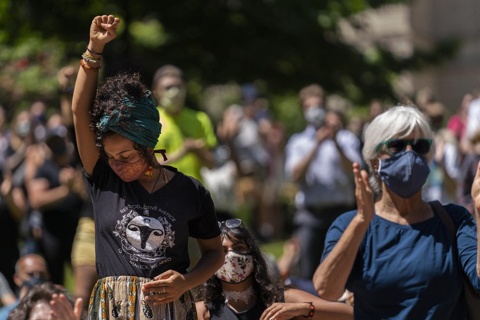 An attendee holds her fist in the air during Rev. E.D. Mondaine's speech at the NAACP's Eulogy for Black America held in the wake of the police killing of George Floyd on May 29, 2019, in Portland, Oregon.