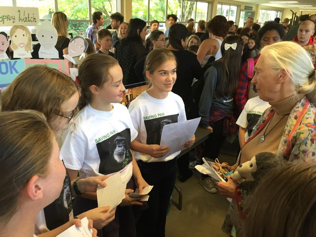 """Brooke Abbruzzese (reading from page) and Talia Baskin (red ponytail band) present the girls' """"Saving Pan"""" cookbook project to Dr. Jane Goodall during a Roots & Shoots event at David Douglas High School in Portland, Oregon, on Oct. 15, 2015. In early 2018, they donated $10,000 from its sales to benefit Goodall's chimpanzee rehabilitation center and sanctuary in the Republic of Congo."""
