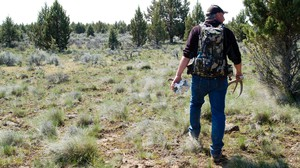 Troy Capps carries deer antlers he found in Central Oregon.