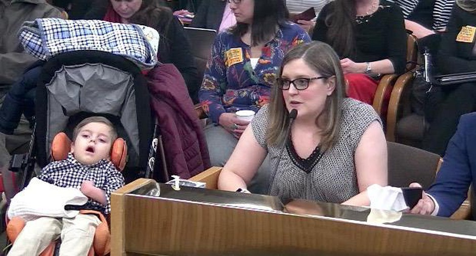 Nikki Monaco and her son Emmett present to a public hearing in Salem.