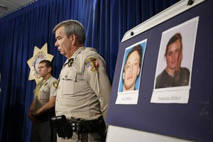Las Vegas Sheriff Doug Gillespie stands by a board with the pictures of Jerad Miller and Amanda Miller, suspected of killing two police officers having lunch at a strip mall pizza buffet. The Millers fatally shot the officers in a point-blank ambush, then fled to a nearby Wal-Mart where they killed a third person and then themselves in an apparent suicide pact, June 9, 2014 in Las Vegas.
