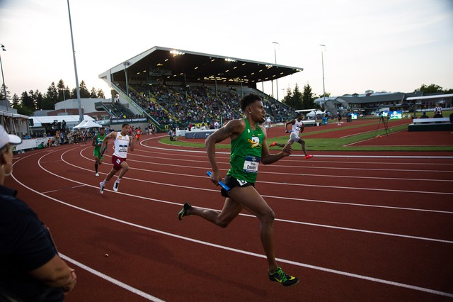 Oregon sprinter Orwin Emilien carries the baton in the 4x400-meter relay. Historic Hayward Field's West Grandstand looms in the background.