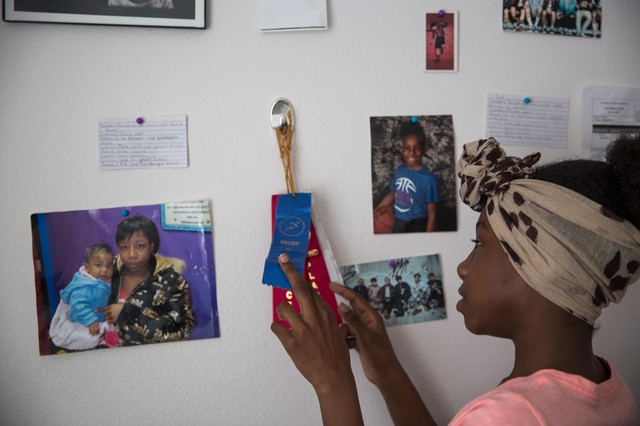 Azaysha looks at ribbons pinned to the wall of her room in Portland, Ore., Wednesday, May 22, 2019. Azaysha's wall includes photos of her family, a drawing a friend made of her, photos of her favorite band, and her first report card with letter grades.