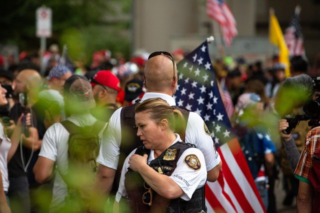 Liaison officers with the Portland Police Bureau monitor a white supremacist rally under the Hawthorne Bridge in Portland, Ore., Saturday, Aug. 17, 2019. The rally carried the potential for violence and attracted hundreds of antifascist counter-protesters.