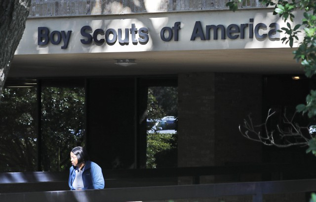 An unidentified woman walks out of the Boy Scouts of America national headquarters building in Irving, Texas, Friday, Nov. 1, 2019.