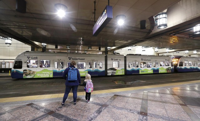 Southbound passengers wait as they look across at a northbound Sound Transit light rail train at an underground station Wednesday, Nov. 6, 2019, in downtown Seattle. State and local governments could end up scrambling to pay for road paving and other transportation projects as a Washington state measure that would cut car tabs to $30 was passing in early returns Tuesday.