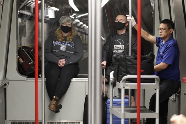 FILE - In this March 2, 2020 file photo, travelers Meredith Ponder, left, and Coleby Hanisch, both of Des Moines, Iowa, wear masks to remind them not to touch their faces as they ride a train at Seattle-Tacoma International Airport in SeaTac, Wash.   The spread of the coronavirus, including cases in the U.S., has many small business owners canceling or changing plans, arranging for staffers to work from home, even asking employees who have traveled to places with widespread outbreaks to stay home for as long as a month.  (AP Photo/Elaine Thompson, File)