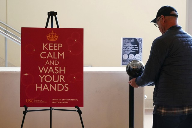 """Detailed view of hand sanitizer station with sign """"Keep calm and wash your hands"""" provided by the University of Southern Califonria environmental health and safety department during an NCAA college basketball game at the Galen Center, Saturday, March 7, 2020, in Los Angeles."""