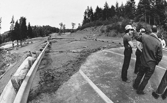 Residents stop and try to remember how the Old 99 Steelhead Drive near Longview used to look before the mud and logs started to cover it from the eruption of Mt. St. Helens, some 50 miles away, May 20, 1980. At least six people are dead and about 100 missing.