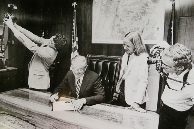1983 Dayshoot organizers Michael Lloyd (left), Cathy Cheney and Michal Thompson (right) stand around Governor Vic Atiyeh (seated) as he signs a gubernatorial proclamation declaring July 15, 1983 to be Oregon Photojournalism Day. All three are back for this year's dayshoot.