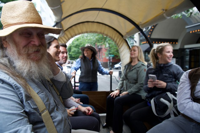 People take a ride in a covered wagon through downtown Portland.
