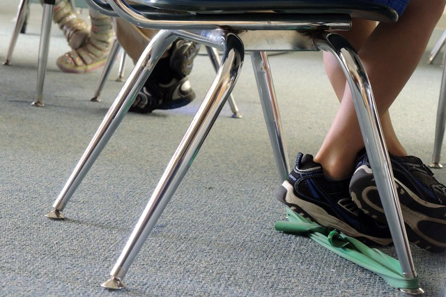 Raiden has a thick green rubber band stretched between the legs of his classroom chair. When he's feeling too energetic to sit still he can tap on the band with his feet.