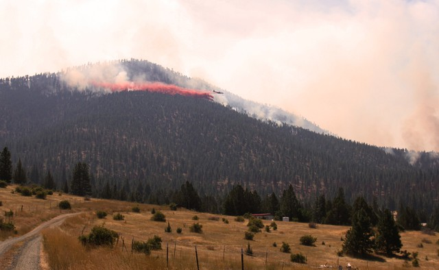 Air tankers make drops in attempt to slow and control the Canyon Creek Complex. About 300 firefighters are in the area to control the fast-moving fire.