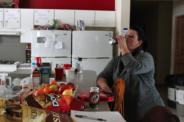 """Melissa Cooper chugs an energy drink while planning the next meal. Cooper is in charge of sorting supplies, cooking, and setting up new arrivals with a place to sleep. """"I'm tired. I'm getting four hours of sleep a night,"""" she said."""