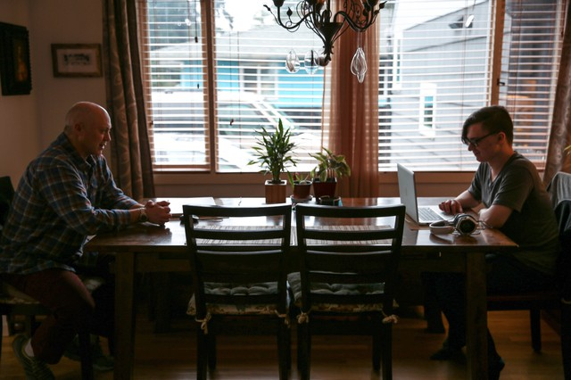 Skylar Isaacs (right) takes online classes as a high school junior at one end of the dining room table. His father Steven often sits across from him.