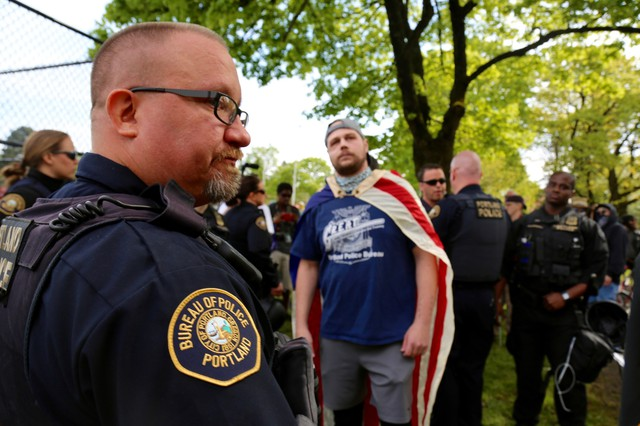 """Jeremy Joseph Christian (center wearing American flag), the man accused of afatal stabbing on the MAX train, attended the April 29 """"March for Free Speech"""" on 82nd Avenue."""
