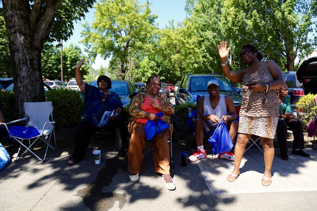 Residents wave as the Good in the Hood parade marched down Martin Luther King Jr. Blvd in Northeast Portland.
