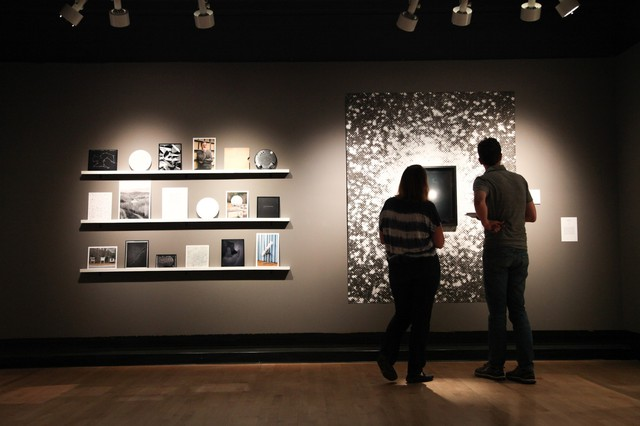 "Curator Julia Bradshaw describes artwork in the eclipse-inspired ""Totality"" exhibit at the Fairbanks Gallery of Art to OPB's Aaron Scott in Corvallis, Oregon."