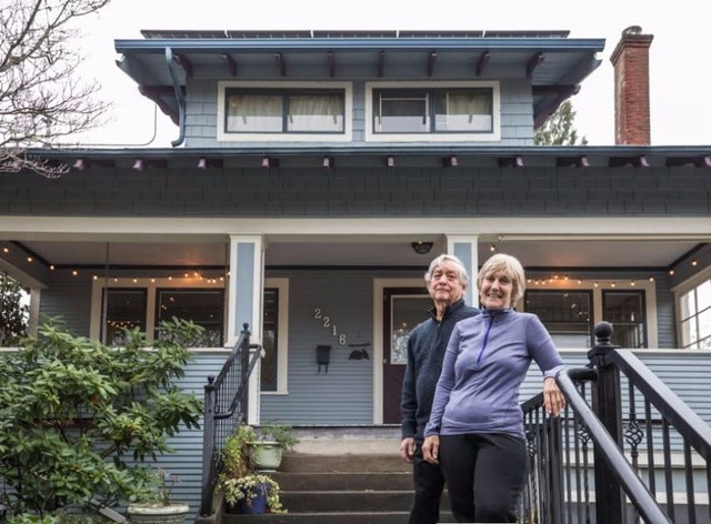 Lynn Merrick and her husband, Michael Kronenthal, pose in front of their Mount Tabor home, which turned out to be less energy-efficient than they expected once they saw their Home Energy Score.