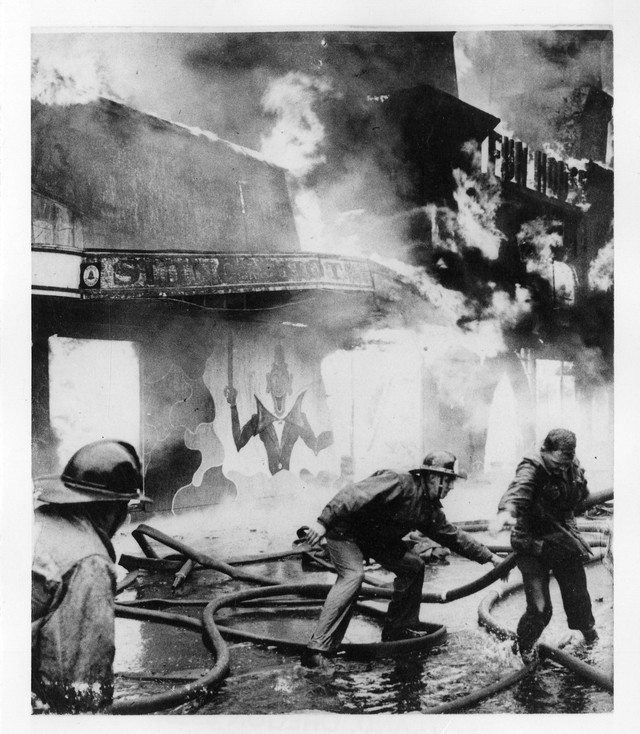 """""""Jantzen Beach Amusement Park fire. Firemen try to move hoses out of the way of building about to collapse,"""" March, 1960."""