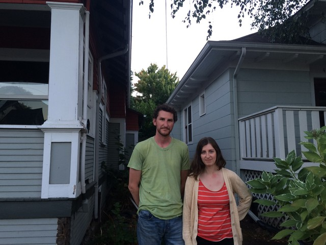 Chris Palochak and Caitlin Poliak stand in between their home, right, and home soon to be demolished. Their 9-month-old daughter's bedroom is only a few feet away from the demolition site. They're worried their 9-month-old daughter could be exposed to lead dust released when walls coated in lead-based paint are demolished.