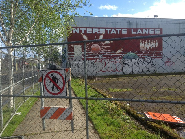 The sidewalk is closed in front of the building that formerly housed Interstate Lanes