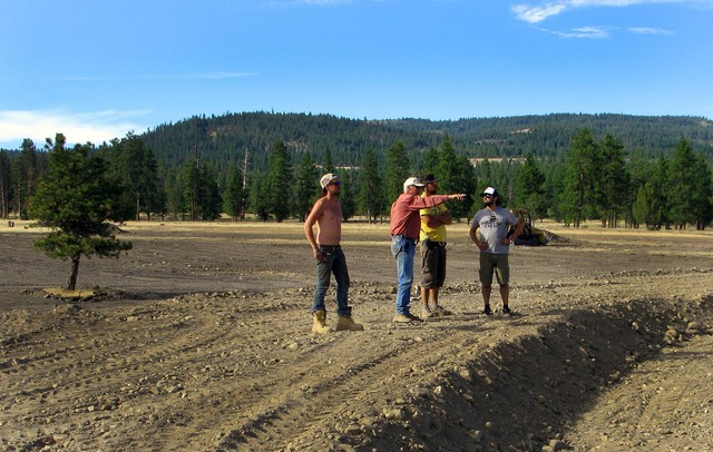 Landowner Craig Woodward (center) gives festival workers directions on earth moving form the top of the earthen amphitheater he shaped from a previously scraped part of land.