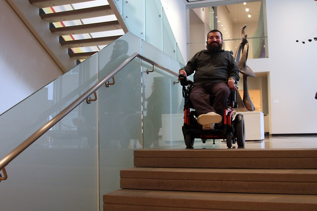 Disability rights advocate Joseph Lowe shows how the warren of stairs and elevators make the museum difficult to navigate for individuals with mobility challenges.