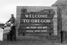 """Dick Sherk next to """"Welcome to Oregon"""" sign (1961)"""