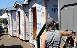 A volunteer works on the construction of new sleeping pods at Portland's Right 2 Dream Too homeless camp on Saturday, July 21, 2018.