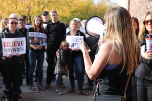 """Moey Newbold speaks to people who rallied at Bend City Hall under banners of """"Believe Survivors,"""" and """"Time's Up."""""""