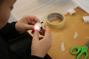 A Tumalo Community school student prepares a light he programmed to go into a student-designed product.