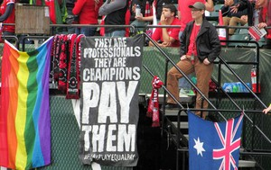 In this photo taken May 21, 2016, a sign calling for equitable pay in soccer is displayed at a Portland Thorns women's soccer game at Providence Park in Portland, Oregon.