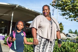 Lydia Gray-Holifield with her daughter, Georgy'e, in front of KairosPDX charter school. Located in the former Humboldt Elementary School, the charter school was threatened with displacement. Portland Public Schools officials have now said the school can stay.
