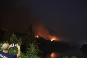 A person snaps a cell phone photo of the Eagle Creek Fire, visible from the nearby town Cascade Locks.
