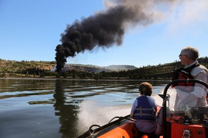 Chris Hooper, right, of White Salmon watches the fire caused by a derailed oil train in Mosier, Oregon, near Hood River in the Columbia River Gorge on Friday, June 3, 2016.