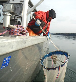 Emiliano Perez with the Nisqually Tribe brings up a plankton net from 400 feet beneath Puget Sound.