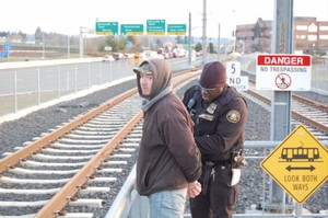 After checking for valid fare, transit police officer Curtis Brown arrests Nicholas Glendon Davis on an identity-theft charge at the end of the light-rail line at Clackamas Town Center.