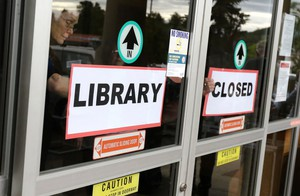 Staff members tape a closed sign to the front door to the Douglas County Library Roseburg branch in May 2017. The branch closed due to budgetary reasons, leaving the city of Roseburg without a public library branch of its own.