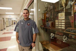 Camas High School Athletic Director Rory Oster in front of one of several trophy cases honoring the Papermakers.
