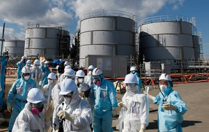 In this Feb. 10, 2016, file photo, members of a media tour group wearing a protective suit and a mask walk together after they receive a briefing from Tokyo Electric Power Co. employees (in blue) in front of storage tanks for radioactive water at the tsunami-crippled Fukushima Dai-ichi nuclear power plant in Okuma, Fukushima Prefecture, northeastern Japan.