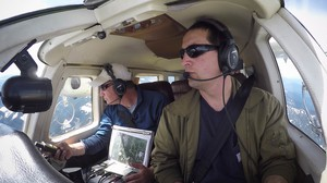 Jeff Lewis (left) listens for signals from below his airplane indicating the presence of fishers below in the Gifford Pinchot National Forest.