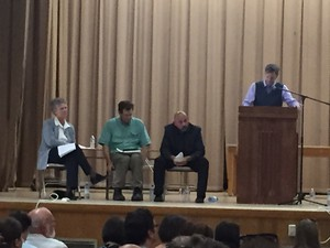 In this May 31, 2016 photo, Portland officials listen as parents voice objections to recent revelations of lead found in school drinking water. From left, Superintendent Carole Smith, Portland Public Schools Board of Directors Chair Tom Koehler, PPS Chief Operating Officer Tony Magliano and Portland-area State Representative Rob Nosse (standing).